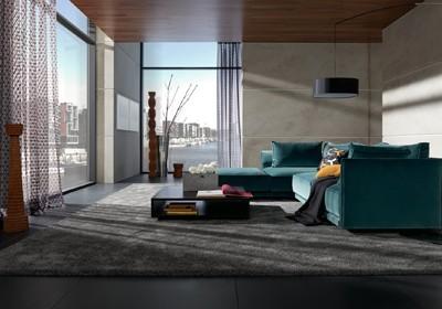 Wohnzimmer mit blauem Sofa und zwei großen Fenstern.