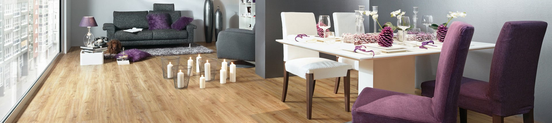Küche mit gedecktem Esstisch und Holzboden. Kerzen stehen neben dem Tisch am Boden.
