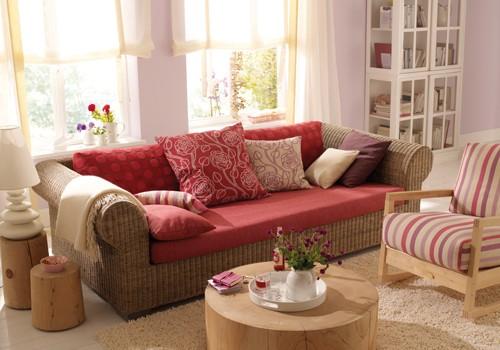 Sofa auf dem verschieden bezogene Kissen liegen, rot und beige, neu gepolstert.