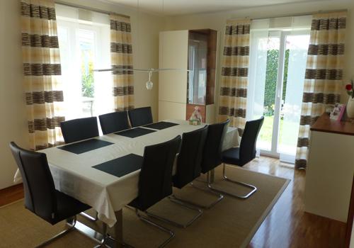 Esszimmer mit dunklen Stühlen und hellen modernen Vorhängen.