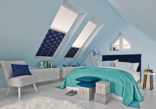 Dachgeschosszimmer mit Doppelbett und Dachfenstern. Die Dachfenster haben einen Sonnenschutz.