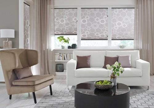 Wohnzimmer mit Sofa und Sonnenschutz.