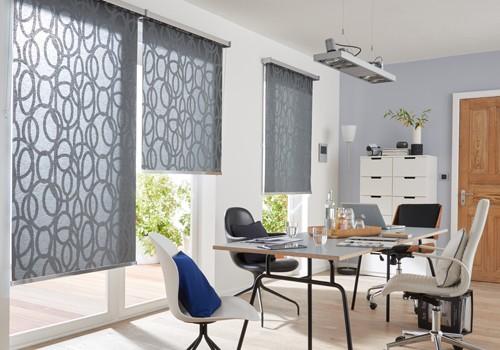 Ein Arbeitsraum mit Schreibtisch und Arbeitsleuchte. Wichtig ist der Sonnenschutz am Fenster.