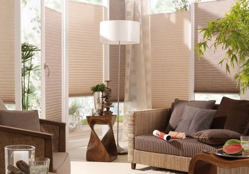 Wohnzimmer mit braun/beigem Sonnenschutz Plissee.
